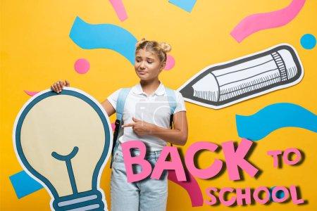 Photo pour Écolière confus pointant du doigt l'ampoule en papier près des éléments décoratifs et le lettrage de retour à l'école sur jaune - image libre de droit