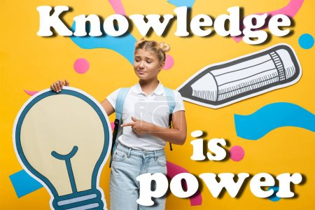 Confused schoolgirl pointing with finger at paper light bulb near decorative elements and knowledge is power lettering on yellow