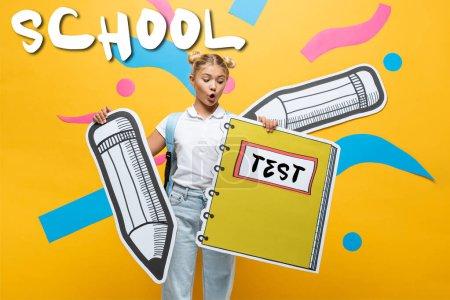 Photo pour Écolier choqué tenant un cahier en papier et un crayon près de l'école et un lettrage d'essai sur du jaune - image libre de droit