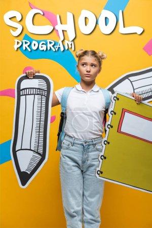 Nachdenkliches Schulkind mit Bleistift und Notizbuch in der Nähe des Schulprogramms Schriftzug auf gelb