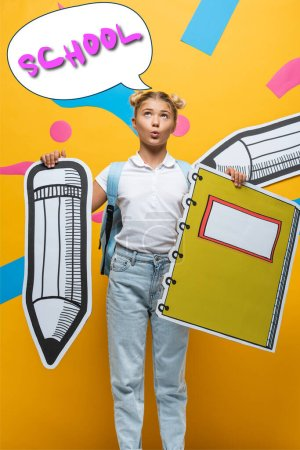 Pensive schoolgirl holding paper pencil and notebook near speech bubble illustration with school lettering on yellow