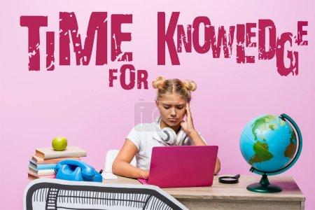 Photo pour Enfant triste dans les écouteurs à l'aide d'un ordinateur portable près du globe, livres, téléphone rétro, temps pour le lettrage des connaissances et l'art du papier sur rose - image libre de droit