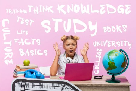 Worried kid looking at camera near laptop, books, paper art, globe, retro telephone and lettering on pink