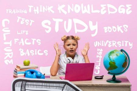Foto de Niño preocupado mirando la cámara cerca de la computadora portátil, libros, arte de papel, globo, teléfono retro y letras en rosa - Imagen libre de derechos