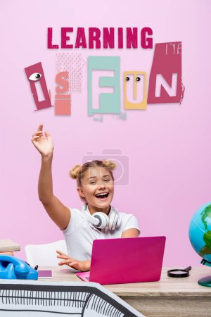 Photo for Schoolgirl sitting with raised hand near laptop, telephone, learning is fun lettering and paper art on pink - Royalty Free Image