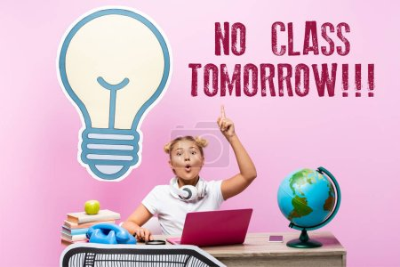 Excited schoolkid having idea near gadgets, paper artwork and no class tomorrow lettering on pink background