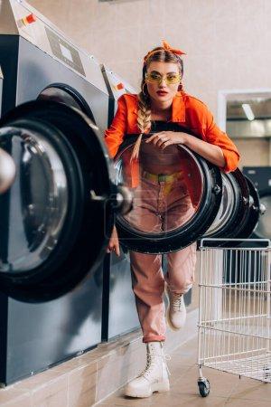 Foto de Enfoque selectivo de la mujer con estilo en gafas de sol mirando a la cámara cerca de lavadoras en lavandería - Imagen libre de derechos
