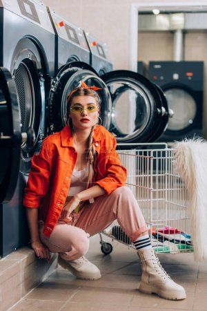 stylish woman in sunglasses sitting near cart with dirty clothing and washing machines in laundromat