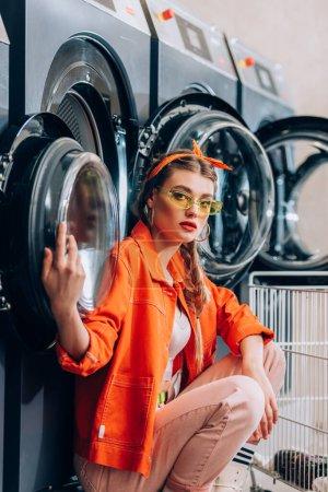 fashionable woman in sunglasses sitting near metallic cart and washing machines in laundromat