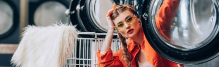 trendy woman in sunglasses sitting near metallic cart with faux fur and washing machines in laundromat, banner