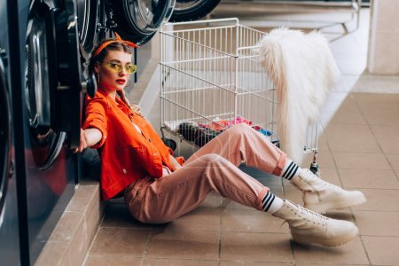 trendy woman in sunglasses sitting on floor near metallic cart with dirty clothing and washing machines in laundromat