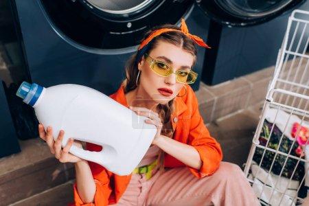 Photo pour Vue grand angle de la jeune femme assise sur le sol et tenant bouteille avec détergent dans la laverie automatique - image libre de droit