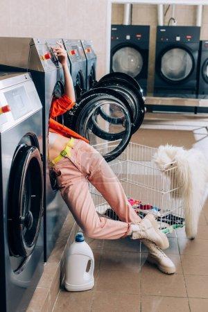 Beine einer neugierigen Frau ragen aus Waschmaschine in der Nähe von Waschmittelflasche und Einkaufswagen mit schmutziger Kleidung
