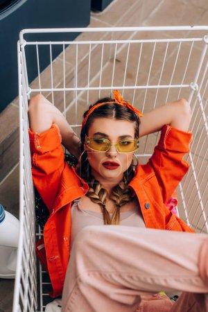 Blick von oben auf eine stilvolle Frau, die im Wäscheservice im Einkaufswagen sitzt