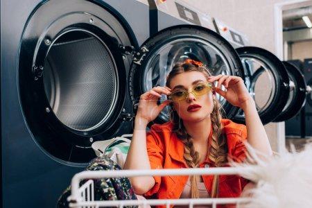 Photo pour Femme élégante touchant des lunettes de soleil et assis dans le chariot près des machines à laver dans la laverie automatique - image libre de droit