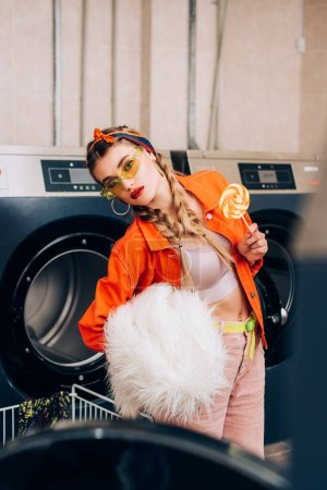 stylish woman in sunglasses holding lollipop and faux fur coat near washing machines in laundromat
