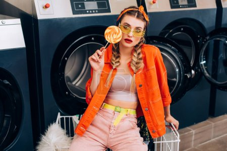 Photo for Trendy woman in sunglasses holding lollipop near cart with clothing and washing machines in laundromat - Royalty Free Image
