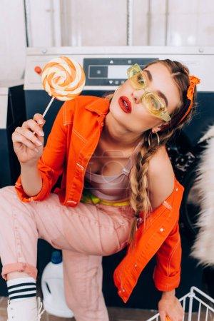 Photo pour Femme à la mode tenant sucette sucrée dans laverie automatique - image libre de droit