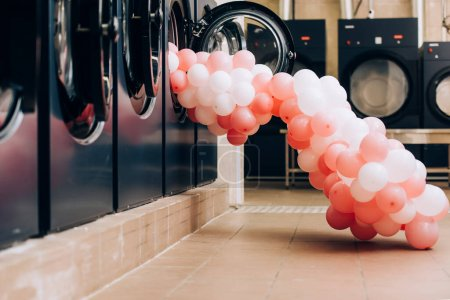 Photo for Pink balloons near modern washing machines in laundromat - Royalty Free Image