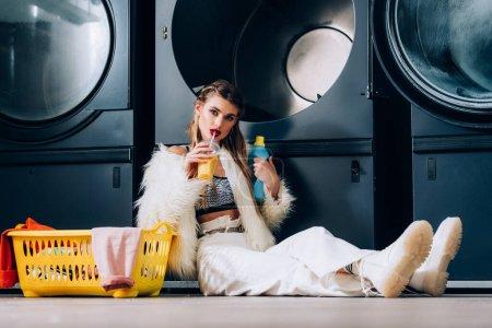 Photo pour Femme élégante veste en fausse fourrure boire du jus d'orange et assis près du panier avec buanderie, bouteille de détergent et lave-linge dans la laverie automatique - image libre de droit
