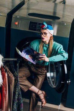 Photo pour Jeune et élégante femme en turban et lunettes de lecture magazine en laverie automatique - image libre de droit