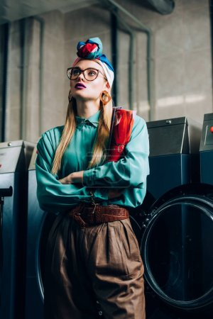 Photo for Young trendy woman in glasses and turban standing with crossed arms and holding magazine in public laundromat - Royalty Free Image