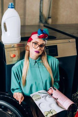 Trendfrau mit Brille und Turban hält Magazin in der Nähe der Waschmaschine im öffentlichen Waschsalon