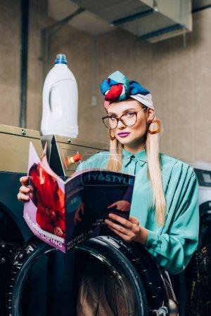 Foto de Mujer en gafas y turbante celebración revista en lavandería - Imagen libre de derechos
