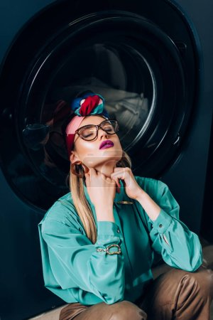 Photo for Stylish young woman in glasses and turban sitting with closed eyes near washing machine - Royalty Free Image
