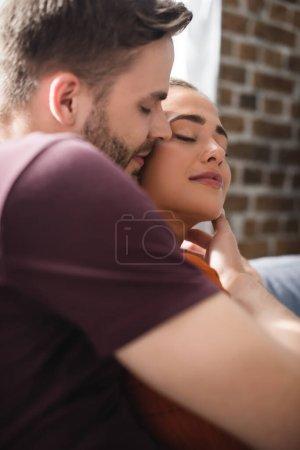 Photo pour Femme heureuse avec les yeux fermés près de l'homme touchant son visage sur le premier plan flou - image libre de droit