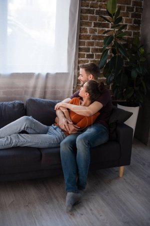 Photo for Young couple embracing while resting on sofa at home - Royalty Free Image