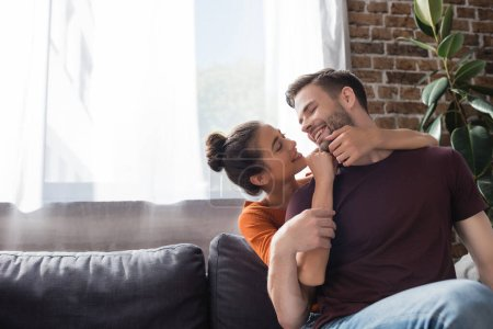 cheerful woman touching face of happy boyfriend while sitting on sofa at home