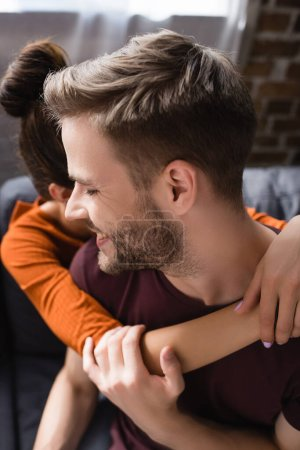 Photo for Happy man embraced by tender girlfriend at home - Royalty Free Image