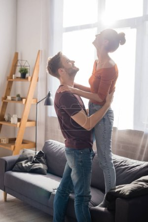 Photo for Side view of young man hugging girlfriend standing on sofa at home - Royalty Free Image