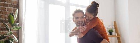 Photo pour Joyeuse femme piggybacking sur heureux petit ami à la maison, bannière - image libre de droit