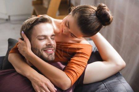 Photo pour Homme heureux avec les yeux fermés embrassé par tendre, femme bien-aimée - image libre de droit