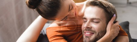 tender young woman hugging and touching head of happy man at home, banner