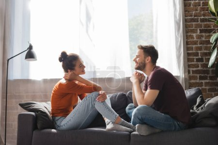 Photo for Side view of young couple sitting on sofa and talking while looking at each other - Royalty Free Image