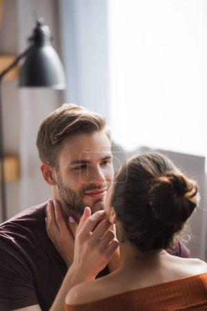 Photo pour Vue arrière de la jeune femme touchant homme souriant tout en se regardant - image libre de droit