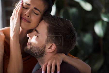 crying woman touching face while embracing beloved man at home