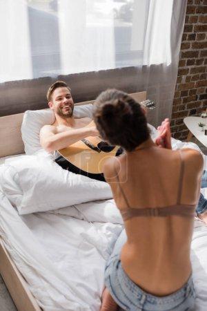 Photo pour Souriant homme couché dans le lit et jouer de la guitare tout en regardant petite amie dansant en soutien-gorge - image libre de droit