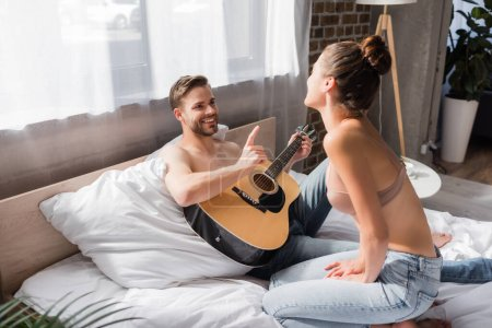 Photo for Smiling man holding guitar and pointing with finger near girlfriend in bra sitting on bed - Royalty Free Image