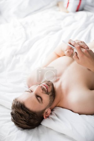 overhead view of shirtless man lying in bed and chatting on mobile phone