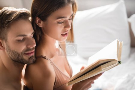 happy man leaning on shoulder of sexy girlfriend reading book in bedroom