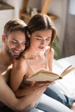 Photo pour Homme heureux avec les yeux fermés embrassant sexy copine livre de lecture dans la chambre - image libre de droit