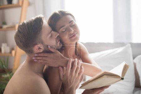 Photo pour Sexy femme tenant livre tandis que torse nu copain toucher et embrasser elle dans chambre - image libre de droit