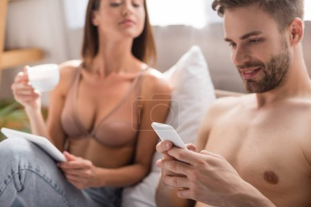 shirtless man chatting on smartphone near woman in bra holding coffee and digital tablet on blurred background