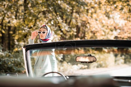 Stylish woman in sunglasses standing near cabriolet car on blurred foreground outdoors