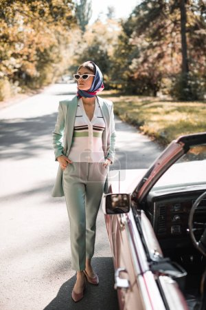 Elegant woman in sunglasses with hands in pockets looking away near car on blurred foreground on road