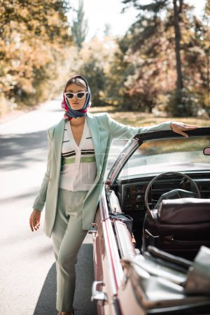 Elegant woman in sunglasses standing near vintage auto during trip on blurred foreground
